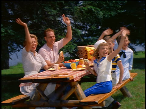 1959 family sitting at picnic table eating / children turning + waving offscreen / industrial