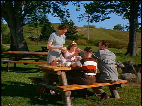 vidéos et rushes de 1949 family sitting at picnic table eating / industrial - pique nique