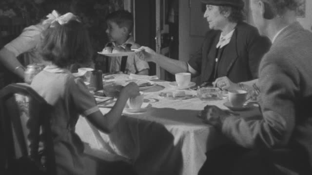 1947 MS Family sitting at table eating dinner together / United Kingdom