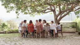 Family sitting at table under tree in yard