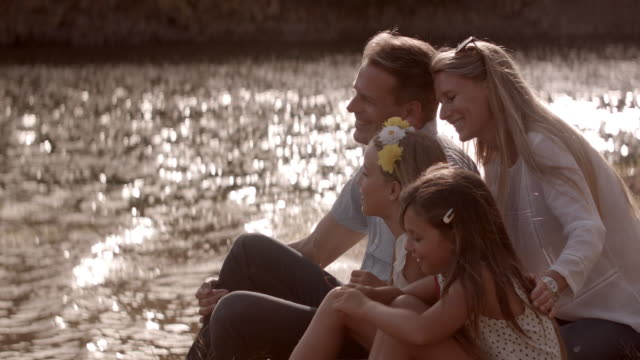Family sitting by lake in evening sunshine