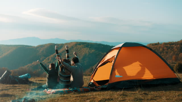 family sitting by the tent and raising hands up in the air on top of the mountain - tent stock videos & royalty-free footage