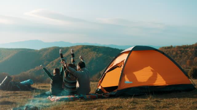 stockvideo's en b-roll-footage met familie zitten bij de tent en verhogen handen omhoog in de lucht op de top van de berg - tent