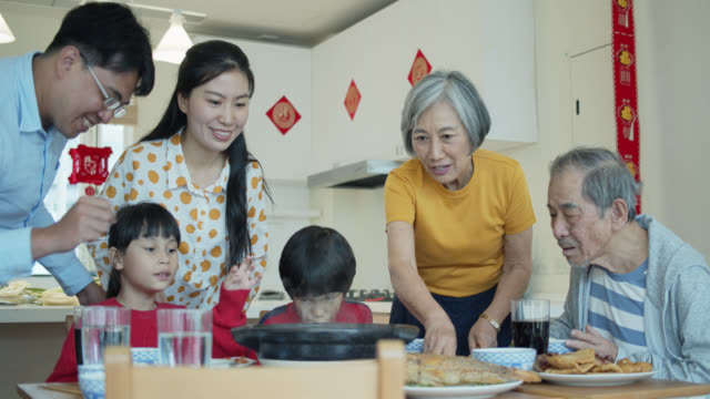 family sitting down and bringing food to table for chinese new year - chinese ethnicity stock videos & royalty-free footage