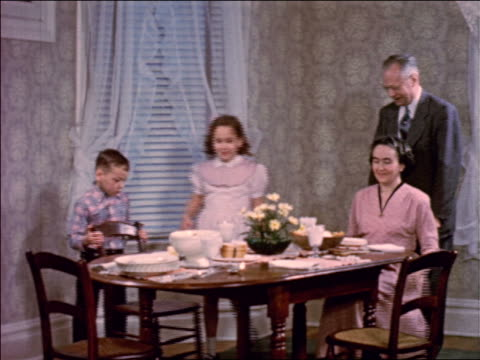 1953 family sitting down at dining room table + saying grace / males hold chairs for females