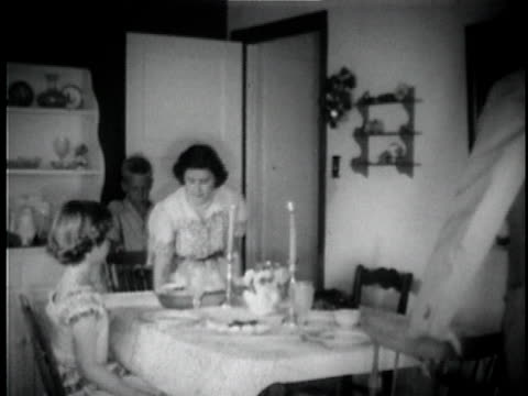 b/w ms family sitting down at dinner table and praying together / usa - マナー点の映像素材/bロール