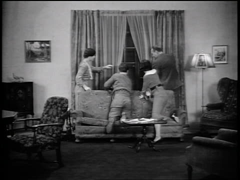 b/w 1935 family sitting in living room / they turn + look out window, hurry off screen / industrial - 1935 stock videos & royalty-free footage