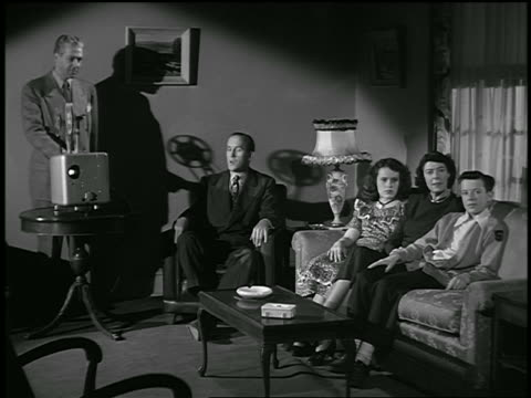 b/w 1949 family sitting in living room watching movies as salesman runs projector / industrial - salesman stock videos and b-roll footage