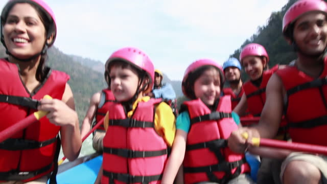 Family sitting on a boat at river rafting