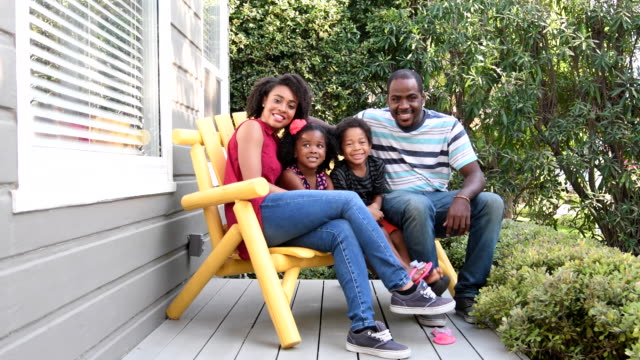 Family sitting on bench on porch smiling