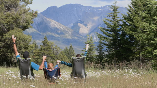 family sitting on camping chairs holding hands and looking at mountains in banff national park in summer. - chair stock videos & royalty-free footage