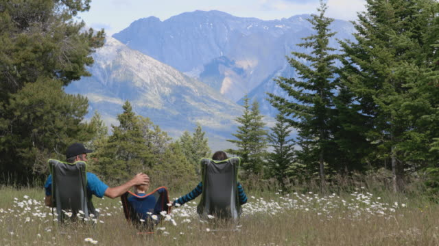 vídeos de stock e filmes b-roll de family sitting on camping chairs holding hands and looking at mountains in banff national park in summer. - membro humano