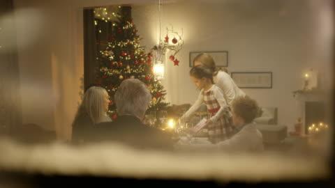 vídeos de stock e filmes b-roll de família sentada na mesa de natal - fairy lights