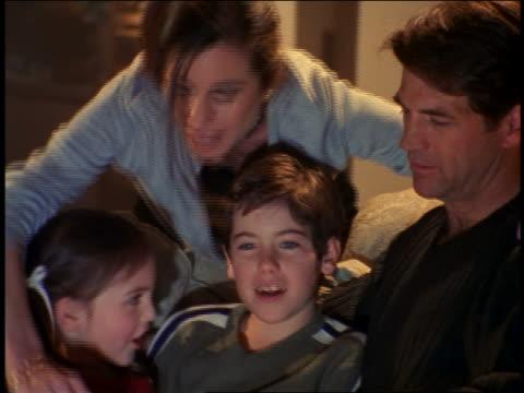 vídeos y material grabado en eventos de stock de family sitting on couch eating popcorn + watching (offscreen) television - 1990 1999