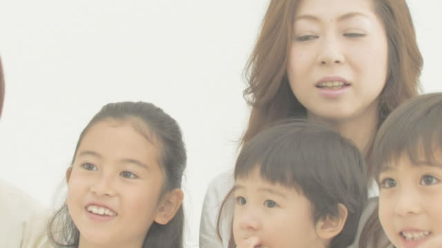 family sitting on couch smiling - 大家族点の映像素材/bロール