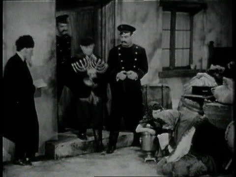 family sitting on couch talking / police removing candlestick menorah from home and kicking them while woman reaches for them - 1946 stock videos & royalty-free footage