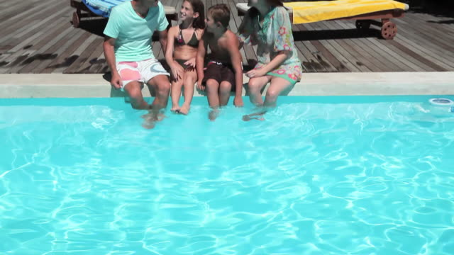 Family sitting on edge of swimming pool