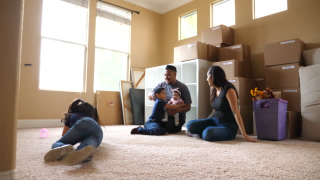 ms family sitting on floor of living room of new home during move in day - latin american and hispanic stock videos & royalty-free footage