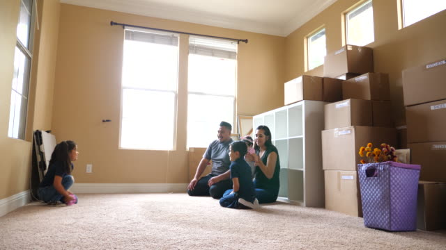 ms family sitting on floor of living room of new home during move in day - two parents stock videos & royalty-free footage