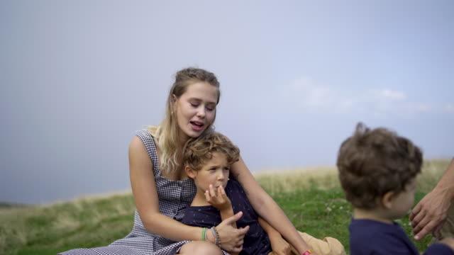 familie sitzt auf berggipfel mit picknick. zwei jungen, mutter und vater - vorschulkind stock-videos und b-roll-filmmaterial