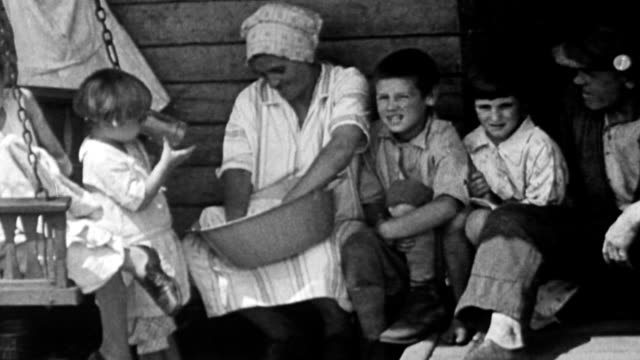 Family sitting on porch during Great Depression / mother kneading bread in bowl / girl sewing on porch swing / crowd of poor children standing and...