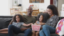 Family Sitting On Sofa At Home Eating Popcorn And Watching Movie Together