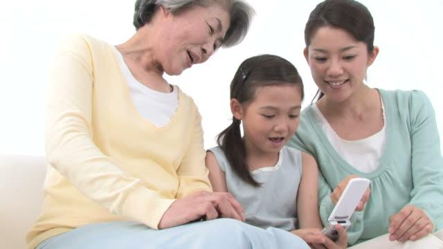 family sitting on sofa, looking at mobile phone - 祖母点の映像素材/bロール