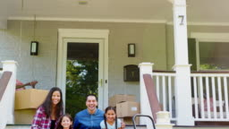 Family Sitting On Steps Of New Home On Moving In Day