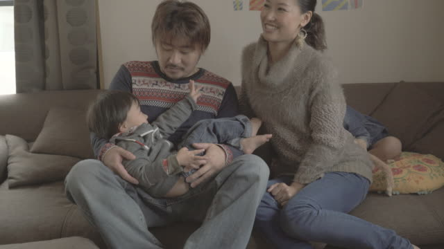 family sitting on the sofa at all - 手提 個影片檔及 b 捲影像