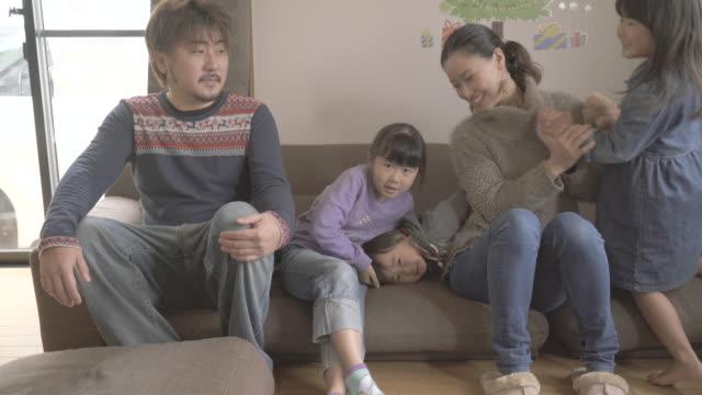 family sitting on the sofa at all - 団らん点の映像素材/bロール