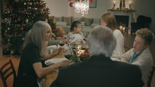 Familie zittend op de tafel voor het kerstdiner.