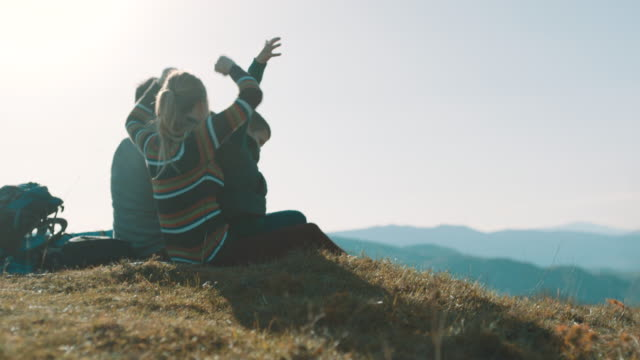 family sitting on top of the mountain and raising hands up in the air - top capo di vestiario video stock e b–roll
