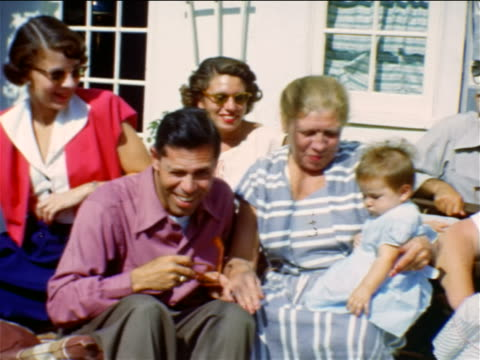 vidéos et rushes de 1950 home movie portrait pan family sitting outside of house posing for camera - petit enfant