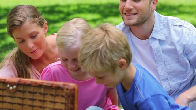Family open a picnic basket to take out slices of watermelon before beginning to eat
