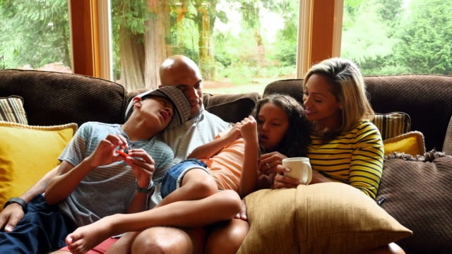 MS Family sitting together on couch in living room
