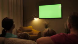 Family Sitting Together Sofa In Their Living Room Night Watching TV Green Screen. Rear View Of Family With Children Sitting On Sofa In Living Room Evening Watching Green Mock-up Screen TV Together.