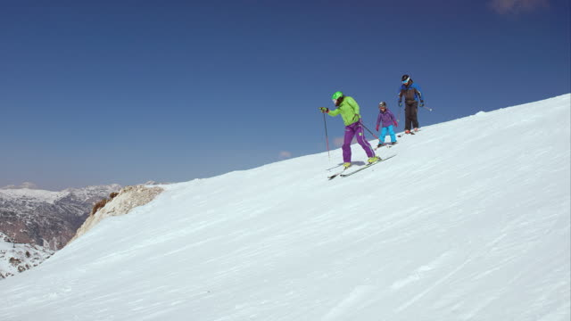 pan family skiing down the slope on a sunny day - ski holiday stock videos & royalty-free footage