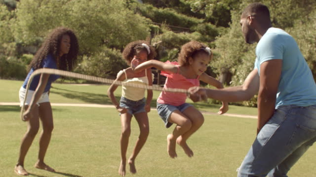 family skipping with rope in park - skipping along stock videos & royalty-free footage