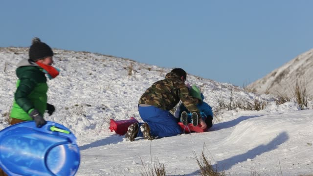 a family sledging on kirkstone pass in the lake district cumbria uk - winter sport stock videos & royalty-free footage