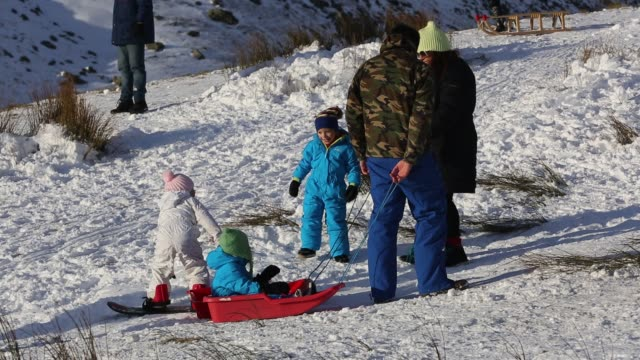 a family sledging on kirkstone pass in the lake district cumbria uk - skiwear stock videos & royalty-free footage