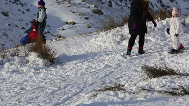 family sledging on kirkstone pass in the lake district, cumbria, uk. - sportswear stock videos & royalty-free footage