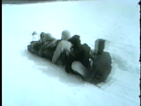 family sleds down snowy hill in a toboggan in chicago in 1962 - anno 1962 video stock e b–roll