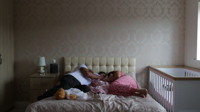 family sleeping together - babygro stock videos & royalty-free footage