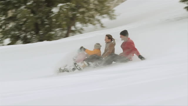 ws pan family sliding down on snowy hill / sun valley, idaho, united states - sledge stock videos & royalty-free footage