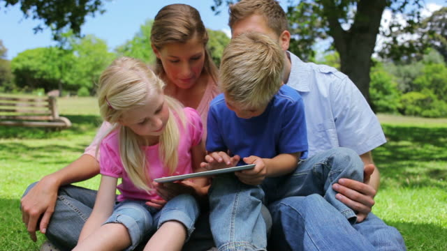 Family sitting together while using a tablet in a park