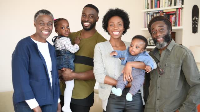 familjen som ler mot kameran med föräldrar som innehar två små barn - flergenerationsfamilj bildbanksvideor och videomaterial från bakom kulisserna