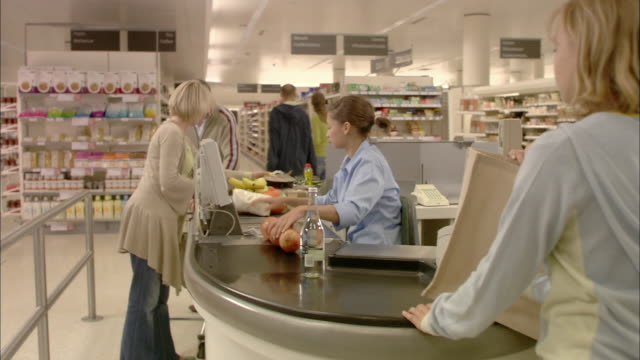 ms family standing at checkout, cashier scanning products and passing to woman / north finchley, london, uk - checkout stock videos and b-roll footage