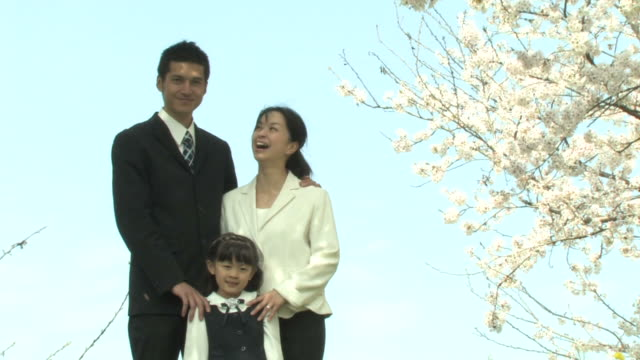 family standing by cherry trees - first day of school stock videos & royalty-free footage