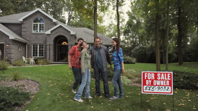 ws family standing in front of house with for sale sign / neenah, wisconsin, usa   - neenah stock videos & royalty-free footage