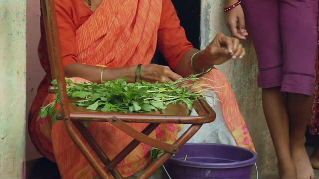 ZO WS Family standing in front of house, woman preparing leaf vegetable / Mumbai, Maharashtra, India